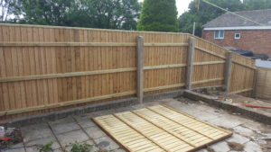 Closboard fencing bolted to existing concrete posts.