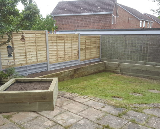Lap panel fencing, on concrete slotted posts, with twin concrete 1ft gravelboards. Used in order to provide support for raised beds