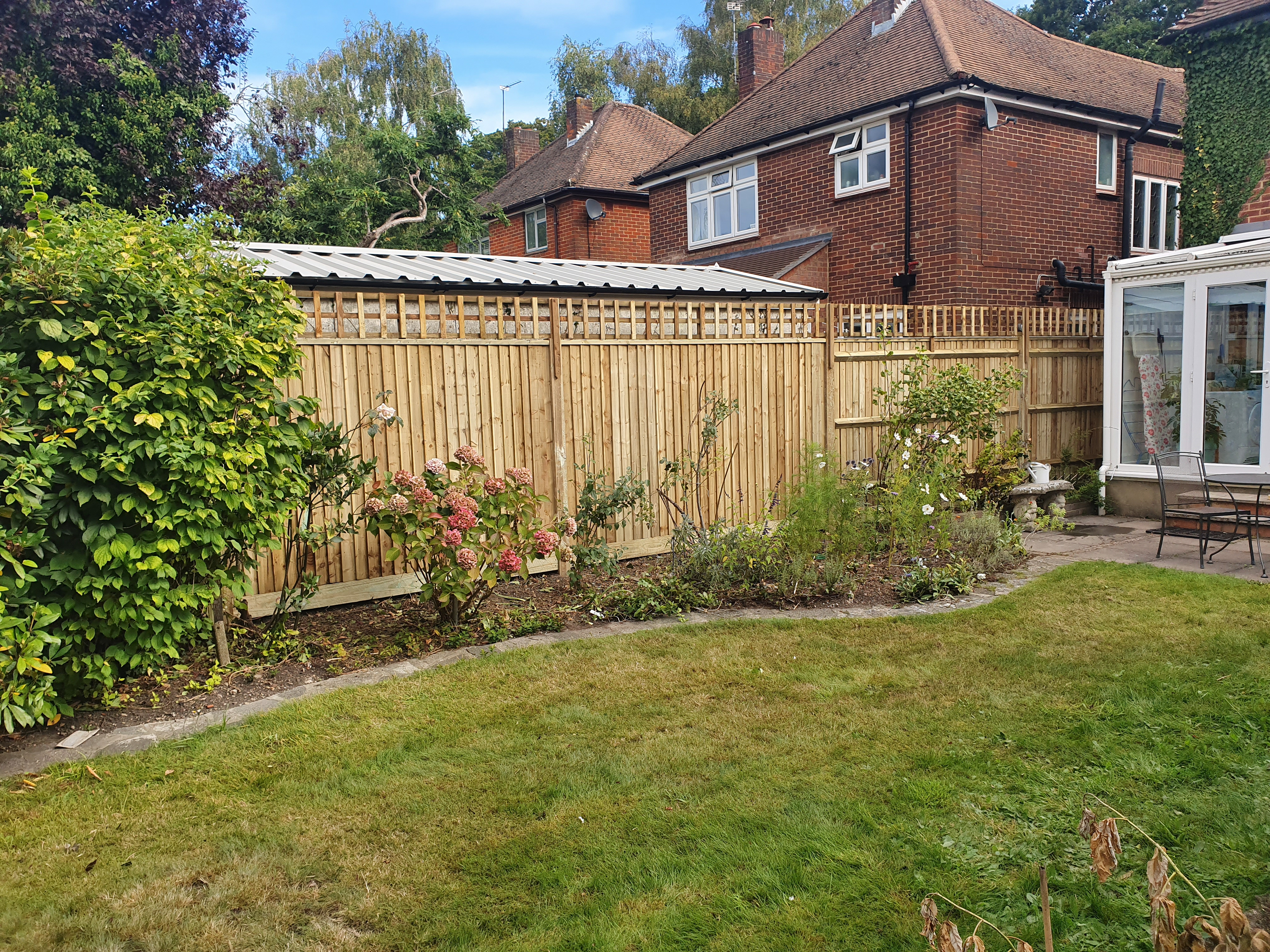 6ft closeboard, on wooden posts and wooden gravelboards. 1ft square trellis installed on top